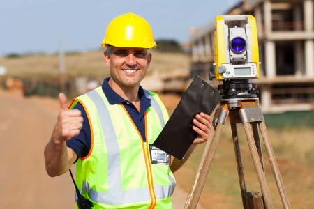 20952593 - senior surveyor giving thumb up on construction site